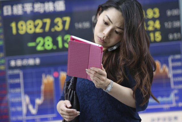 A woman looks at a tablet in front of electronic stock board of a securities firm in Tokyo, Friday, July 10, 2015. Asian stock rose for a second day on Friday as the Greek government proposed a broad financial overhaul to its creditors and Beijing's attempts to arrest a sharp slide in the Chinese market appeared to be working. But most Asian markets were still in the red from a week earlier. (Photo by Koji Sasahara/AP Photo)