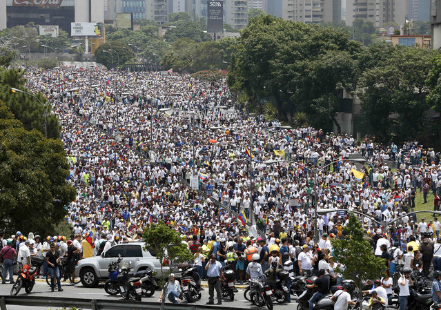 Anti-government protesters march along a highway in Caracas, Venezuela, Wednesday, April 19, 2017. (Photo by Ariana Cubillos/AP Photo)