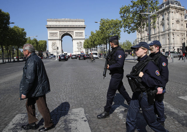 Police officers patrol on the Champs Elysees boulevard in Paris, Friday, April 21, 2017. France began picking itself up Friday from another deadly shooting claimed by the Islamic State group, with President Francois Hollande convening the government's security council and his would-be successors in the presidential election campaign treading carefully before voting this weekend. The Arc de Triomphe is seen in background. (Photo by Christophe Ena/AP Photo)
