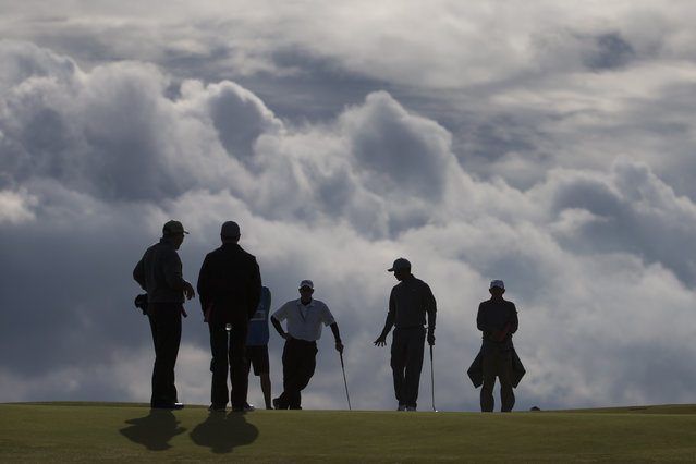 Tiger Woods of the United States, second right, walks across the 11th green during a practice round at St Andrews Golf Club prior to the start of the British Open Golf Championship, in St. Andrews, Scotland, Monday, July 13, 2015. (Photo by Jon Super/AP Photo)