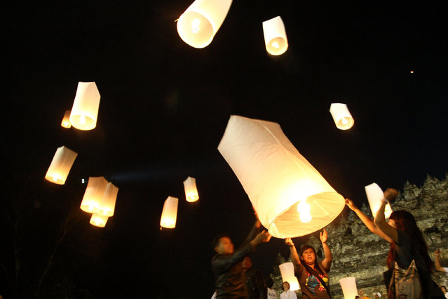 "Buddhist followers release lanterns into the air on Borobudur temple during Vesak Day, commonly known as ""Buddha's birthday"", at the Borobudur Mahayana Buddhist monument on May 28, 2010 in Magelang, Central Java, Indonesia. (Photo by Ulet Ifansasti/Getty Images)"