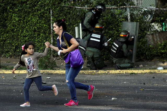 A woman and a girl run away as riot security forces and demonstrators clash during a protest against Venezuela's President Nicolas Maduro's government in Tariba, Venezuela May 9, 2017. (Photo by Carlos Eduardo Ramirez/Reuters)
