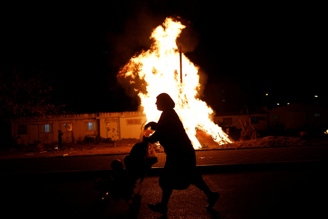 An Ultra-Orthodox Jewish woman walks with a stroller near a bonfire, as she celebrates the Jewish holiday of Lag Ba'Omer in the city of Ashdod, Israel May 25, 2016. (Photo by Amir Cohen/Reuters)