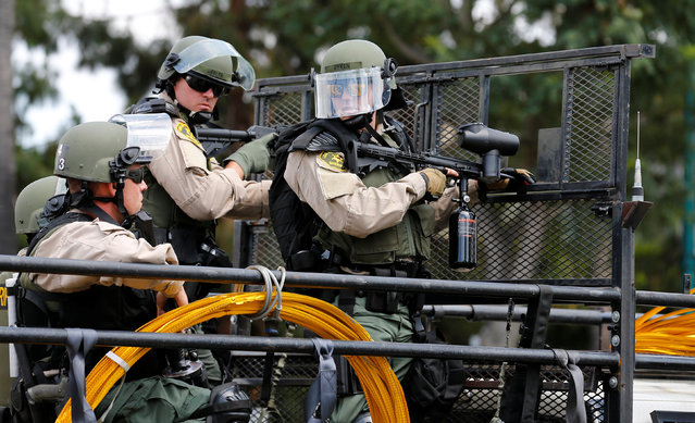 Los Angeles Sheriff Department deputies stand with non-lethal weapons behind a truck mounted barrier to disperse demonstrators after U.S. Republican presidential candidate Donald Trump spoke at a campaign event in Anaheim, California, U.S., May 25, 2016. (Photo by Mike Blake/Reuters)