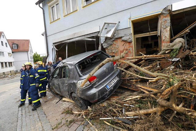 Firefighters stand by a car damaged by floods in the town of Braunsbach, Germany, May 30, 2016. (Photo by Kai Pfaffenbach/Reuters)