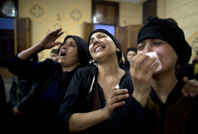 Relatives of killed Coptic Christians grieve during their funeral at Abu Garnous Cathedral in Minya, Egypt, Friday, May 26, 2017. Egyptian officials say dozens of people were killed and wounded in an attack by masked militants on a bus carrying Coptic Christians, including children, south of Cairo. (Photo by Amr Nabil/AP Photo)