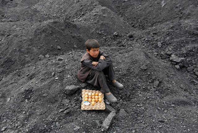 An Afghan boy selling boiled eggs waits for customers at a coal dump site on the outskirts of Kabul, Afghanistan March 7, 2017. (Photo by Mohammad Ismail/Reuters)