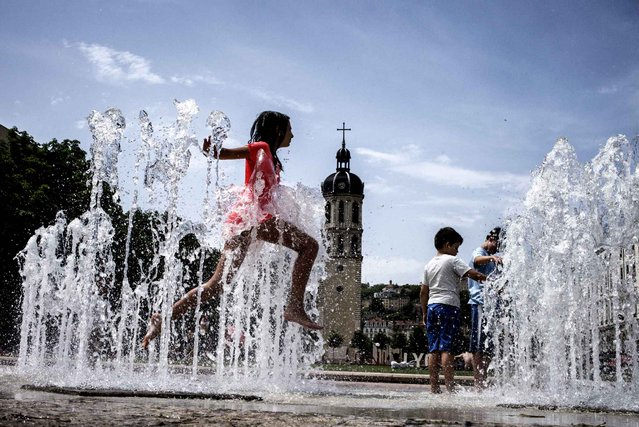 A child cools off in a fountain, on June 9, 2014 in Lyon. (Photo by Jeff Pachoud/AFP Photo)