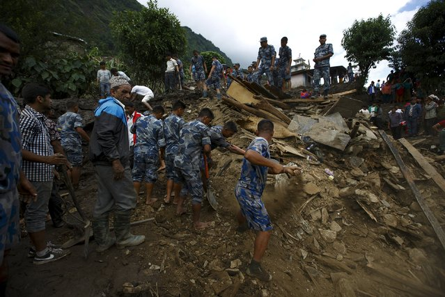Rescue team members search for the landslide victims at Lumle village in Kaski district July 30, 2015. Landslides triggered by torrential rain in Nepal swept through villages on Thursday, killing at least 30 people close to the nation's most popular trekking circuit, home ministry officials said. (Photo by Navesh Chitrakar/Reuters)