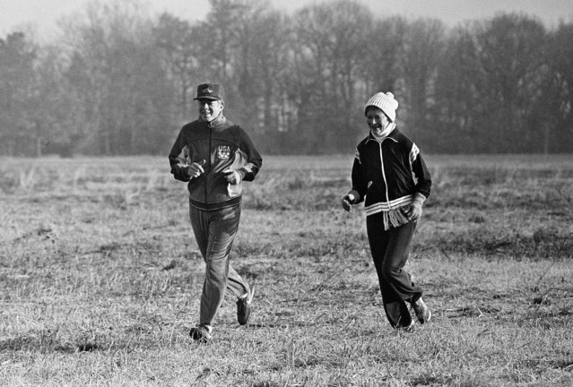 Former U.S. President Jimmy Carter and his wife Rosalynn jog across a frosty field in Plains, Ga., January 24, 1981. (Photo by Charles Kelly/AP Photo)