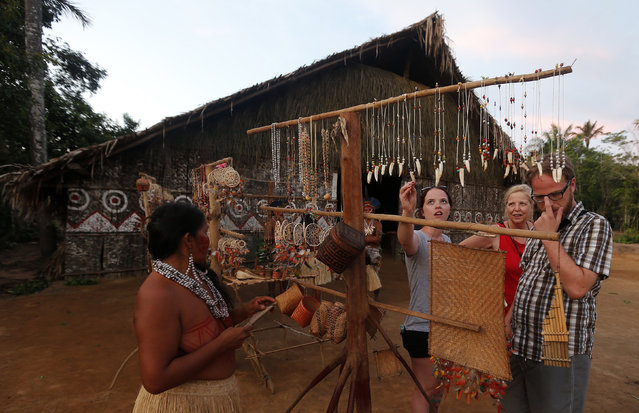 Tourists look at crafts made by members of the Amazonian Tatuyo tribe in their village in the Rio Negro (Black River) near Manaus city, a World Cup host city, June 23, 2014. Because of their proximity to host city Manaus and their warm welcome, the Tatuyo have enjoyed three weeks of brisk business thanks to the World Cup. Usually, they host between 10 and 30 tourists a day. During the World Cup, this number has rocketed to 250 a day, They have become richer and other communities now come to them to sell them juices and fishes. (Photo by Andres Stapff/Reuters)