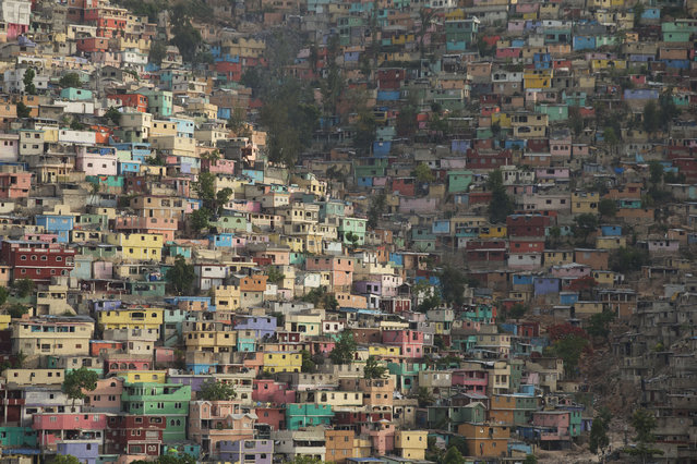 In this June 29, 2015 photo, houses pack a hillside in the Jalousie district of Port-au-Prince, Haiti. Haiti suffered from a severe housing shortage even before the 2010 earthquake. According to a January 2015 report by Amnesty International, the earthquake further increased the deficit. Meanwhile reconstruction efforts focused on building temporary shelters over permanent housing. (Photo by Rebecca Blackwell/AP Photo)