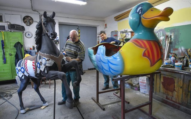 Painter and decoration worker Sandor Valik Zagyva (L) paints one of the horse as maintenance worker Robert Kerek works on one of the duck of Debrecen Amusement Park's carousel in the park's maintenance shop in Debrecen, Hungary, 10 January 2020. One of the most lavish elements of the establishment are the carousel's wooden horses, made in Vienna in the 19th century, which have kept visitors entertained since 1960. During the winter the park's various game elements are constantly being renewed for spring opening. (Photo by Zsolt Czegledi/EPA/EFE)