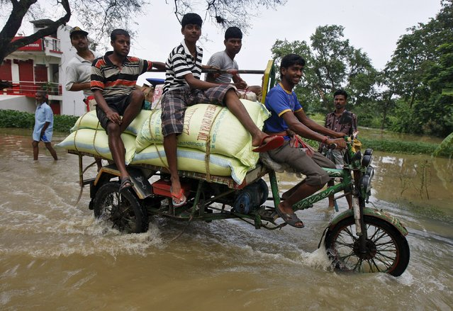 Volunteers transport relief supplies on a motor rickshaw through the flood waters at Howrah district in West Bengal, India, August 5, 2015. (Photo by Rupak De Chowdhuri/Reuters)