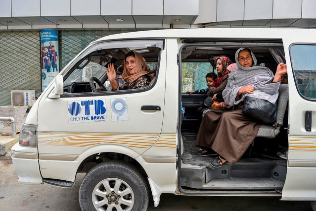 In this photo taken on October 31, 2019, Razia Dalili (front seat) gestures as she drives a mini-bus to carry women passengers in Kabul. A first-of-its kind service called Pink Shuttle is helping women navigate the many challenges they face getting around Kabul, where a woeful lack of transport options is compounded by the risk of harassment if they walk on the streets. (Photo by Wakil Kohsar/AFP Photo)