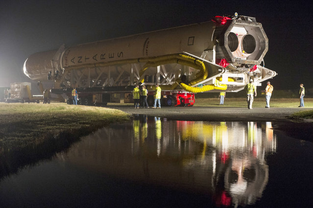 The Orbital Sciences Corporation Antares rocket, with the Cygnus spacecraft onboard, is rolled out of the Horizontal Integration Facility (HIF) to the launch pad on July 10, 2014, at NASA's Wallops Flight Facility, Wallops Island, Virginia. The Antares will launch with the Cygnus spacecraft filled with over 3,000 pounds of supplies for the International Space Station, including science experiments, experiment hardware, spare parts, and crew provisions. (Photo by Bill Ingalls/NASA via Getty Images)