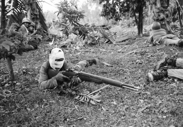 A wounded Vietnamese ranger, his head heavily bandaged with only slits for the eyes and mouth, is ready with his weapon to answer a Viet Cong attack during battle in Dong Xoai on June 11, 1965