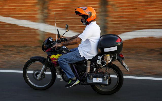 "Ricardo Azevedo rides his Honda NX 200 motorbike, which he converted to be powered by water, in Salto, northwest of Sao Paulo, Brazil, August 6, 2015. The Sao Paulo civil servant built the motorbike which can cover up to 500 kilometres (311 miles) fueled by just one liter of water. Dubbed ""Moto Power H2O"", the bike is powered by a process of electrolysis by which the water molecule is broken down into its constituent elements. (Photo by Nacho Doce/Reuters)"