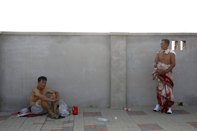 An injured man (R) looks on near the site of the explosions at the Binhai new district in Tianjin, China, August 13, 2015. (Photo by Reuters/China Daily)