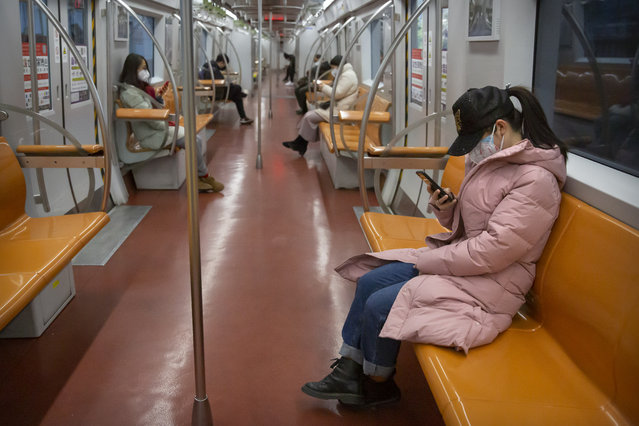 People wearing face masks ride a mostly empty subway train during the morning rush hour in Beijing, Monday, February 3, 2020. Much of China officially went back to work on Monday after the Lunar New Year holiday was extended several days by the government due to a virus outbreak, but China's capital remained largely empty as local officials strongly encouraged non-essential businesses to remain closed or work from home. (Photo by Mark Schiefelbein/AP Photo)