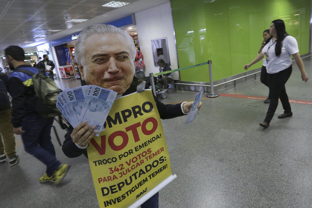 """An activist protests, dressed with a mask of Brazil's President Michel Temer, as he holds fake 100 Brazilian Real notes and a sign that reads in Portuguese """"I buy votes"""", at the arrivals area of the airport in Brasilia, Brazil, Tuesday, August 1, 2017. Temer faces a congressional vote on his future Wednesday, a showdown coming in a month dreaded by leaders of Latin America's largest nation. (Photo by Eraldo Peres/AP Photo)"""