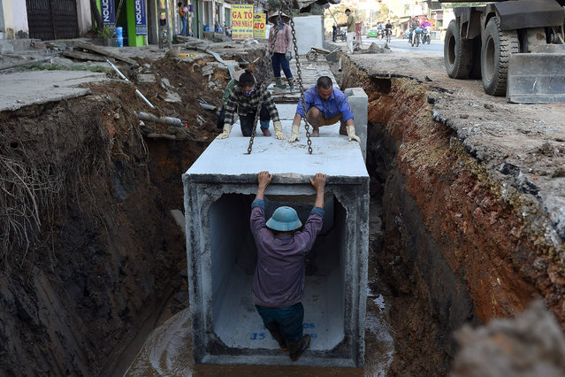 Workers install underground drainage on a street in Hanoi on December 4, 2019. (Photo by Nhac Nguyen/AFP Photo)