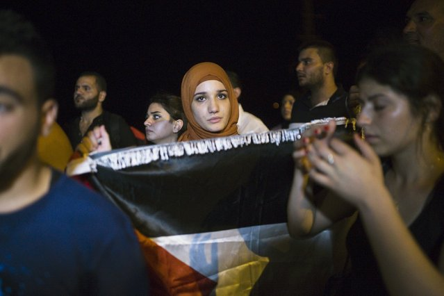 A Palestinian woman holds a Palestinian flag as she attends a protest in support of a hunger-striking Palestinian prisoner, Mohammed Allan, in the southern city of Ashkelon August 16, 2015. (Photo by Amir Cohen/Reuters)