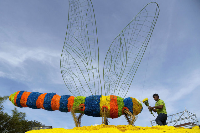A man works in a giant dragon-fly structure of flowers, during the Flower Festival in Medellin, Antioquia department, Colombia on July 31, 2014. (Photo by Raul Arboleda/AFP Photo)
