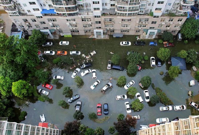 Automobiles are seen flooded at a neighbourhood in Wuhan, Hubei province, China July 9, 2016. Picture taken July 9, 2016. (Photo by Darley Shen/Reuters)
