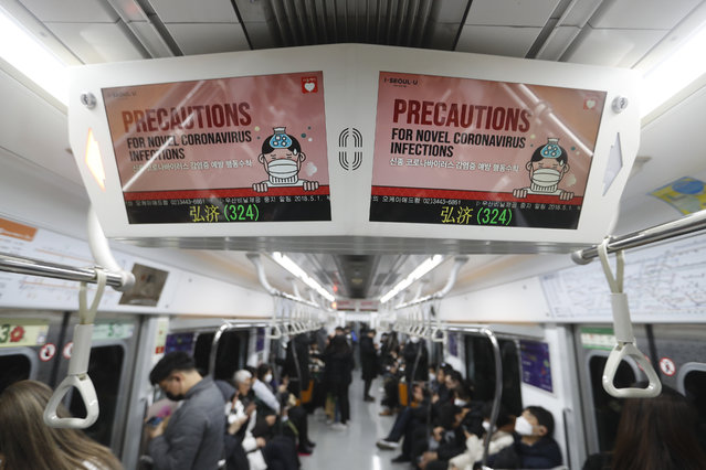 Electric screens about precautions against the illness COVID-19 are seen in a subway train in Seoul, South Korea, Monday, February 17, 2020. Chinese authorities on Monday reported a slight upturn in new virus cases and 105 more deaths for a total of 1,770 since the outbreak began two months ago. (Photo by Ahn Young-joon/AP Photo)