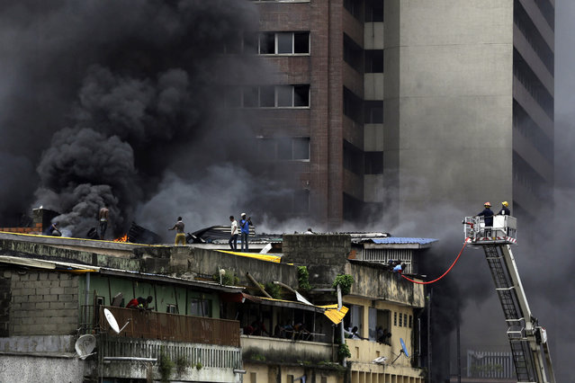 Smoke rises from a fire in downtown Lagos, Nigeria, Tuesday, November 5, 2019. (Photo by Sunday Alamba/AP Photo)