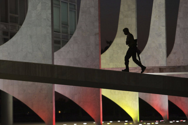 A soldier walks up the ramp of the Planalto Presidential Palace, illuminated with the colors of Spain, in honor of the victims of the Barcelona attack, at dawn in Brasilia, Brazil, Friday, August 18, 2017. Spanish police shot and killed five people carrying bomb belts who were connected to the Barcelona van attack that killed at least 13, as the manhunt intensified for the perpetrators of Europe's latest rampage claimed by the Islamic State group. (Photo by Eraldo Peres/AP Photo)