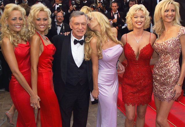 """Playboy magazine president Hugh Hefner (C) poses with playmates 14 May 1999 on the steps of the Palais des Festivals before the screening of their movie """"Entrapment"""" in selection for the 52nd Cannes Film Festival. (Photo by Pascal Guyot/AFP Photo)"""