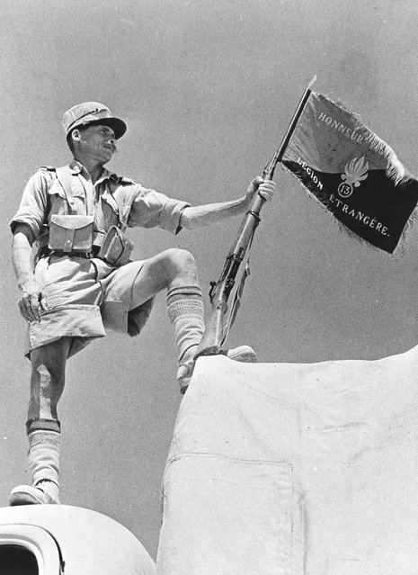 A soldier of the French Foreign Legion holding his regiment's banner at Bar Hacheim in Libya, circa 1940. (Photo by Three Lions)