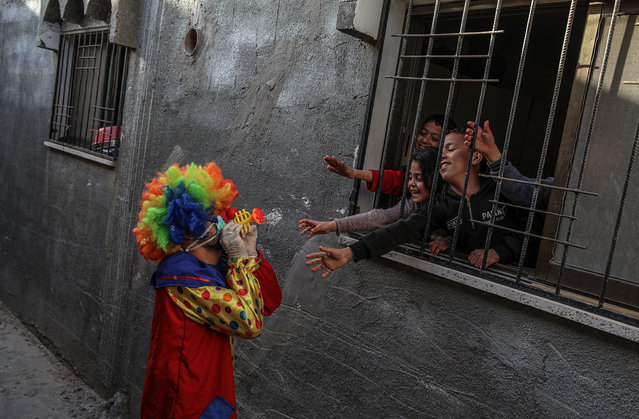 A Palestinian clown wears a protective face mask while entertaining children staying at their home due a precautionary measure against the spread of the coronavirus, in Khanyounis refugee camp, southern Gaza Strip, 03 April 2020. (Photo by Mohammed Saber/EPA/EFE)