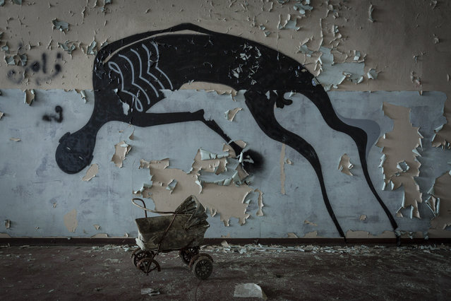 A dolls pram creepily sits underneath some graffiti. (Photo by Thomas Windisch/Caters News)