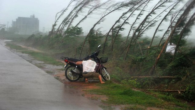 A man takes shelter amid strong rainfall alongside his motorbike in Zhanjiang, south China's Guangdong province on September 16, 2014. A powerful typhoon slammed into China's Hainan island after sweeping past Hong Kong where it disrupted flights and forced the closure of the stock market and container ports. (Photo by AFP Photo)
