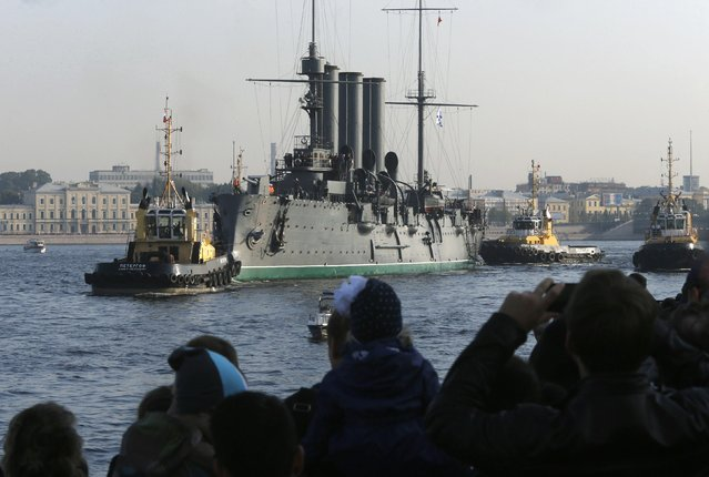 """People watch tug boats towing the """"Cruiser Aurora"""" along the Neva River in the central part of St. Petersburg, September 21, 2014. (Photo by Alexander Demianchuk/Reuters)"""