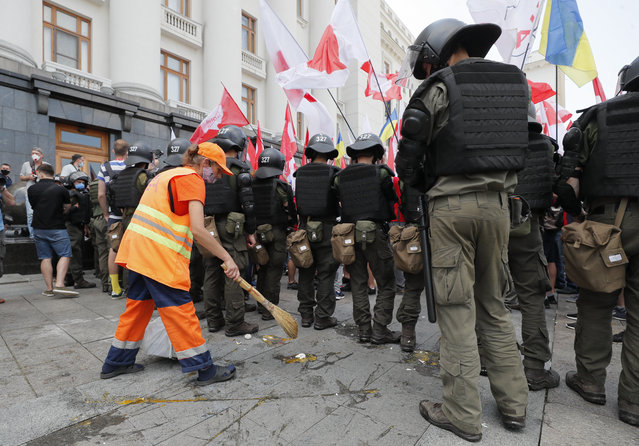"A city worker sweeps up broken eggshells from the street behind a formation of Ukrainian police officers clad in riot gear after far-right militants attacked members and supporters of the Party of Shariy taking part in a protest rally in front of the Presidential Office in Kiev, Ukraine, 17 June 2020. The activists supporting the conservative Eurosceptic party led by populist journalist Anatoly Shariy gathered under the slogan ""The dumb president"" as they lambasted Ukrainian President Volodymyr Zelensky for what they perceive as his failure to implement his election campaign promises. (Photo by Sergey Dolzhenko/EPA/EFE)"