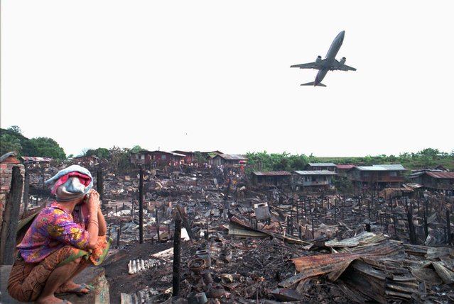 A crying woman sits near remains of houses in Tawau Saturday, September 16, 1995, which were burnt by explosion after a Malaysian Airlines plane crashed on the shantytown on Borneo Island, 725 miles east of Kuala Lumpur, Friday. The plane crash killed 34 of the 53 people on board. (Photo by C. F. Tham/AP Photo)