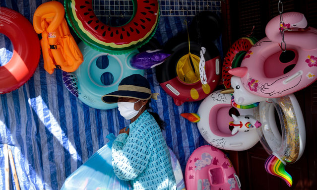 A vendor wearing a face mask, amid concerns over the spread of the COVID-19 coronavirus, sells inflatable toys in her shop in Hua Hin beach area in Thailand on May 19, 2020. Thailand's economy is expected to shrink more than six percent this year as the coronavirus outbreak shatters the country's crucial tourism industry, with all flights into the country banned until the end of June. (Photo by Jack Taylor/AFP Photo)