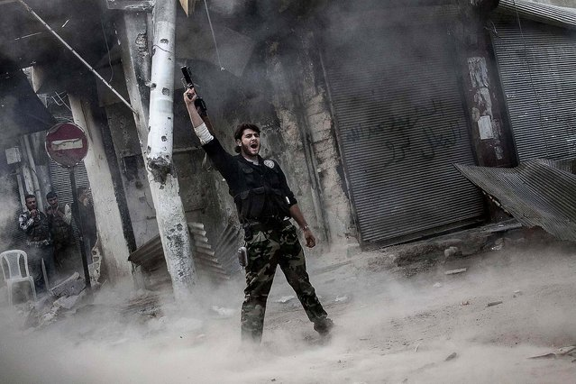 A rebel fighter claims victory after he fires a shoulder-fired missile toward a building where Syrian troops loyal to President Bashar Assad are hiding while they attempt to gain terrain against the rebels, during heavy clashes in the Jedida district of Aleppo, November 4, 2012. (Photo by Narciso Contreras/Associated Press)