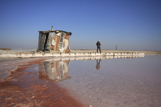 A worker walks along a salt production facility at the Sasyk-Sivash lake near the city of Yevpatoria in Crimea, October 5, 2014. (Photo by Pavel Rebrov/Reuters)