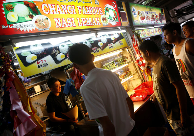 "Stall helper Din Mohammad Rasheed, 50, attends to customers at Changi Famous Nasi Lemak stall at Changi Village Food Center in Singapore August 8, 2016. ""Although nasi lemak is not an expensive food, the quality of the ingredients must be good, so customers come back"", Din said. (Photo by Edgar Su/Reuters)"