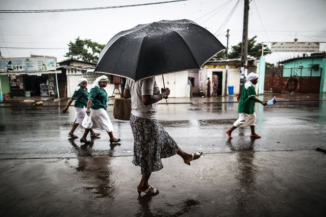 A woman washes a her foot with water streaming out of a pipe as catholic nuns leave the St. Michel Church in Libreville on August 28, 2016 after the Sunday's service. (Photo by Marco Longari/AFP Photo)