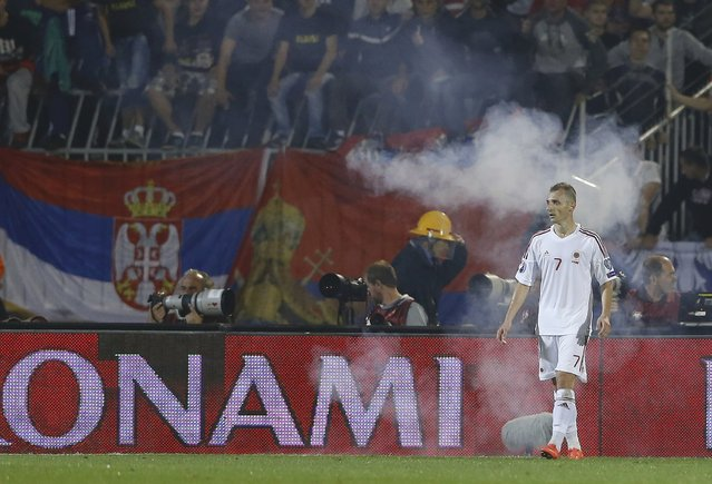 Ansi Agolli of Albania walks amidst smoke from flares during their Euro 2016 Group I qualifying soccer match against Serbia at the FK Partizan stadium in Belgrade October 14, 2014. The politically-sensitive Euro 2016 qualifier between Serbia and Albania was abandoned on Tuesday following a brawl between players from both sides after a flag stunt. (Photo by Marko Djurica/Reuters)
