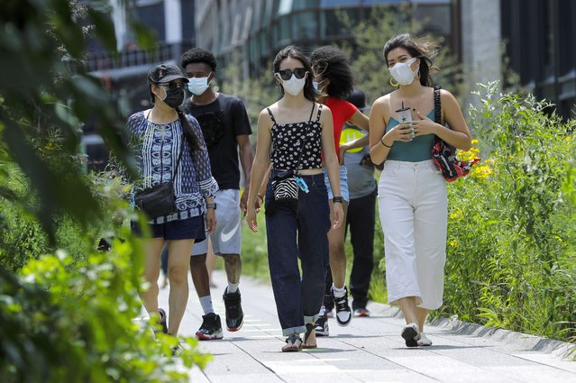 People wearing protective masks during the coronavirus pandemicwalk along the High Line Park, Thursday, July 16, 2020, in New York. The Highline opened today after having been closed the last few months during the pandemic. (Photo by Frank Franklin II/AP Photo)