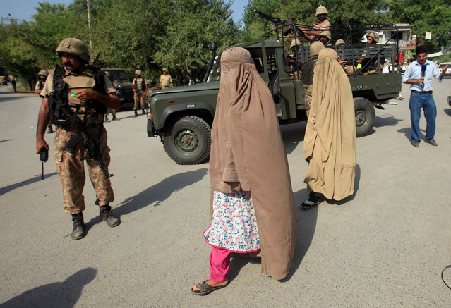 Women walk past army soldiers, who are standing guard at a street, after suicide bombers attacked a Christian neighbourhood in Khyber Agency near Peshawar, Pakistan, September 2, 2016. (Photo by Fayaz Aziz/Reuters)