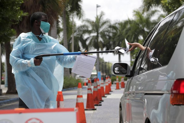 Healthcare worker Dante Hills, left, passes paperwork to a woman in a vehicle at a COVID-19 testing site outside of Marlins Park, Monday, July 27, 2020, in Miami. The Marlins home opener against the Baltimore Orioles on Monday night has been postponed as the Marlins deal with a coronavirus outbreak that stranded them in Philadelphia. (Photo by Lynne Sladky/AP Photo)