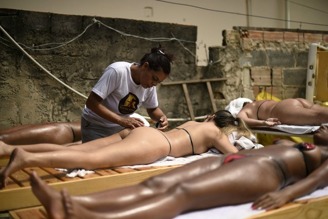 "Esthetician Adriana Alves Moniz, nicknamed Drica, 42, applies insulating tape on her customers as they sunbathe at her beauty center in Belo Horizonte, Brazil, on December 21, 2017. Brazilian women take advantage of the beginning of the summer to sunbathe using the new national trend: natural tanning with insulating tape. Instead of using tiny bikinis on the beach, women avoid being bothered or stalked by getting taped in the shape of them, and lay in the sun over rooftops to enjoy the morning sun and get the perfect ""marquinha"" tan lines. To avoid being ogled by passers by, they tan on specially designed rooftops where beauticians water them down – and even remove the sticky tape which is perfect for tanning because it stays in place. It has become a very lucrative business for local entrepreneurs including Erika Romero Martins, 34, who has one of the most popular ""clinics"" in Rio. As many as 30 women a day travel as far as three hours brown themselves on the 40-square-foot rooftop patio she owns. ""We've found the perfect way for women to get a s*xy bikini top and bottom tan line that does away with the fuss of trying to get the same results with bikini straps that move"", she said last year. ""My clinic is dedicated to getting the best results in a safe and private environment where we take all the right sunscreen and sun protection precautions. The tape stays in a fixed position and produces a clear and sharp contrast on the body between the tanned and untanned area and when it's peeled off it looks amazing"". Appointments cost R$70 ($21) each, with R$50 ($16) top ups later-on to maintain the look. Sessions start at 6am and finish at midday every day, with customers using sun loungers and deck chairs for up to an hour and 20 minutes. (Photo by Douglas Magno/AFP Photo)"